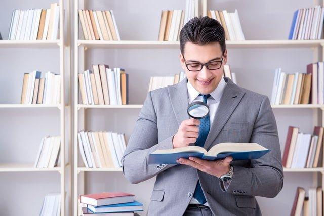 虫眼鏡で本を見るビジネスパーソン