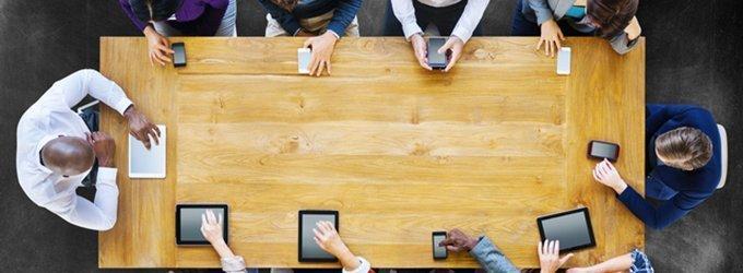 机を囲んでデジタル機器を操作する人々